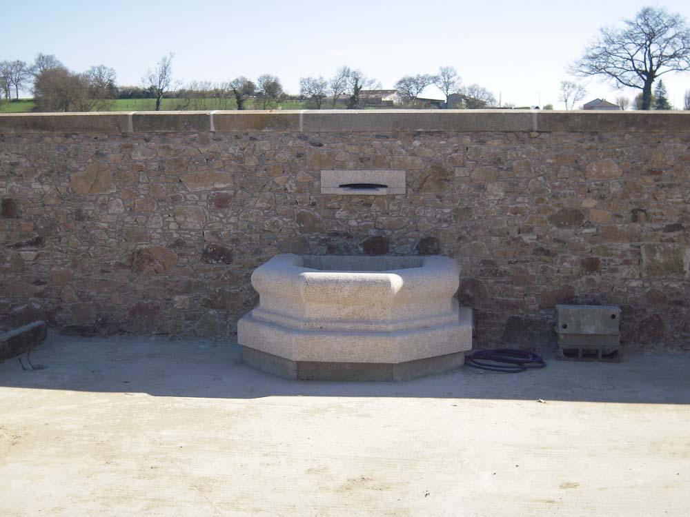 Création d'un mur en maçonnerie de pierre et pose d'une fontaine en granit